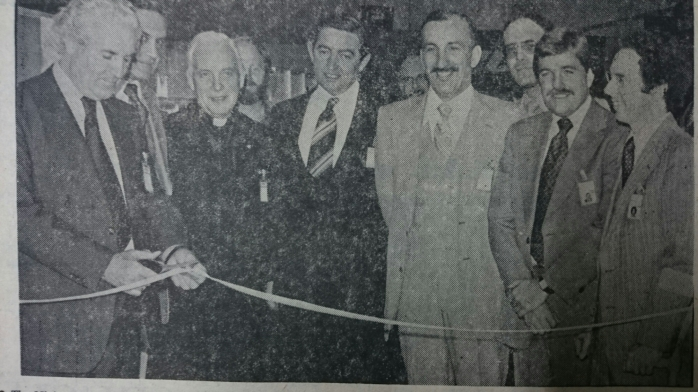 The Minister for Education, Mr. John Wilson, T.D., cuts the tape to officially open the new Bose factory at Carrickmacross. Pictured along with top management are Monsignor Morris, Archdeacon, Carrickmacross (third from left) and Mr. Stanley. A. Hendryx, Managing Director (extreme right)