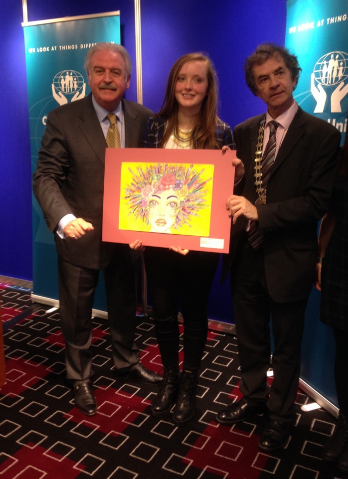 Sarah Leddy from Inniskeen is congratulated by compere Marty Whelan (left) and Martin Sisk, President ILCU (right), for winning first place in the Credit Unions' annual Art Competition (11-13 category). Photo: ILCU